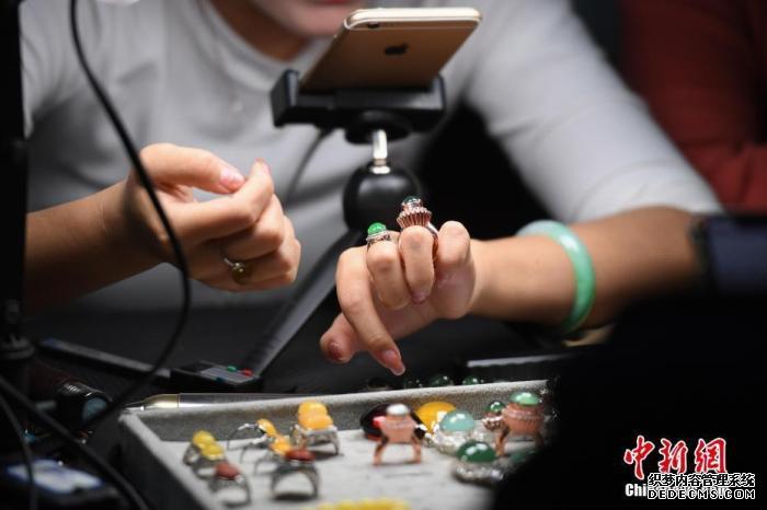 资料图:在瑞丽市姐告经济特区的玉城淘宝直播基地,一名主播通过手机向顾客展示货物。/p中新社记者 刘冉阳 摄